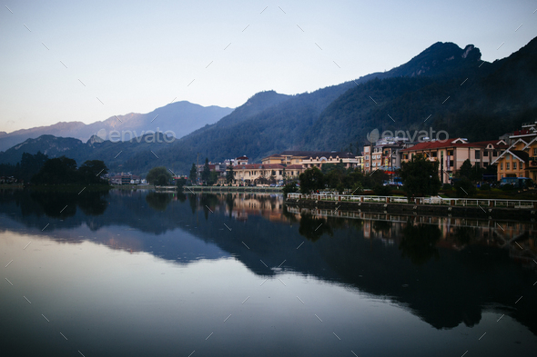 Buildings and mountains reflected in a small lake. - Stock Photo - Images