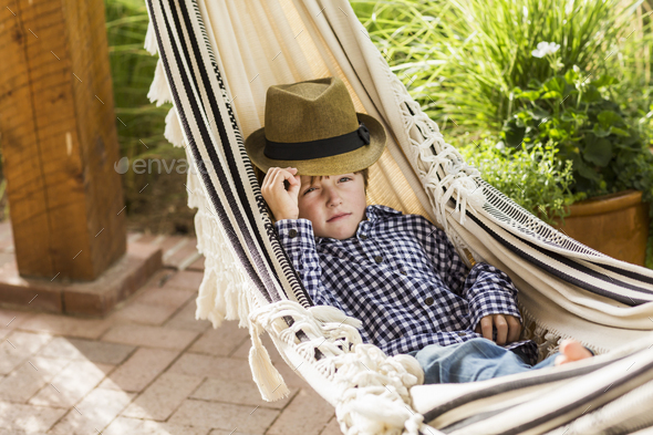 portrait of 6 year old boy lying in hammock on porch - Stock Photo - Images