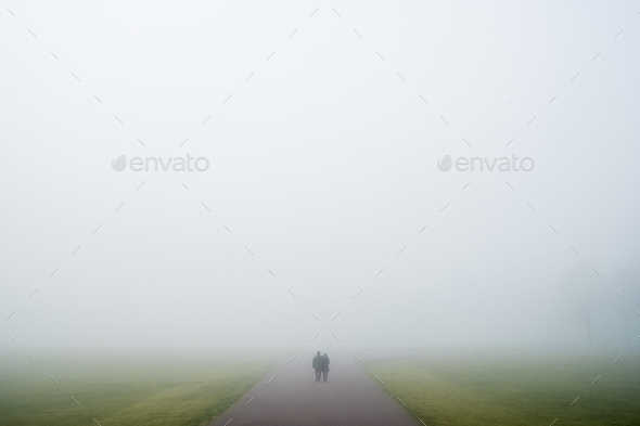 Two people walking along a rural road on a misty day. - Stock Photo - Images