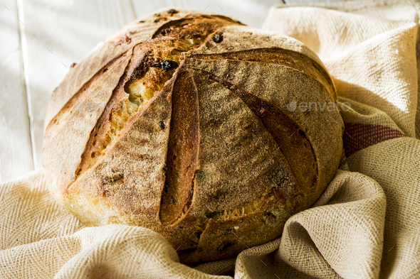 High angle close up of a freshly baked round loaf of bread on tea towel. - Stock Photo - Images