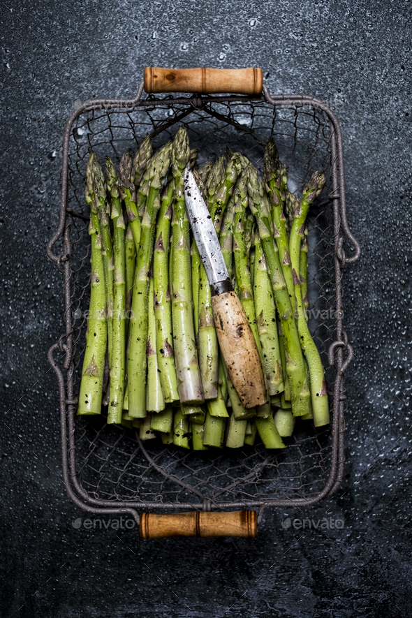 High angle close up of freshly picked green asparagus in metal basket. - Stock Photo - Images
