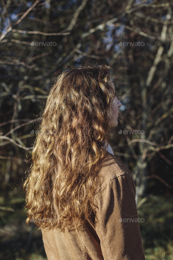 View from behind of teenage girl with long, wavy, brown hair - Stock Photo - Images