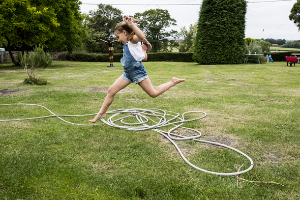 Girl wearing denim dungarees jumping over a garden hose on a lawn. - Stock Photo - Images