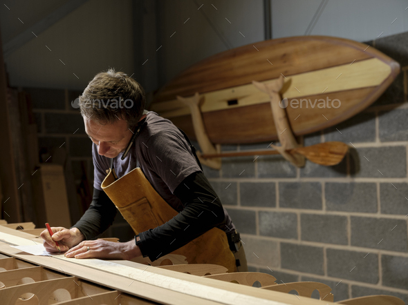 Paddleboard maker using mobile phone in workshop - Stock Photo - Images