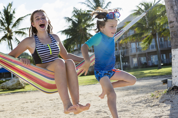 13 year old girl in hammock with her 5 year old brother - Stock Photo - Images