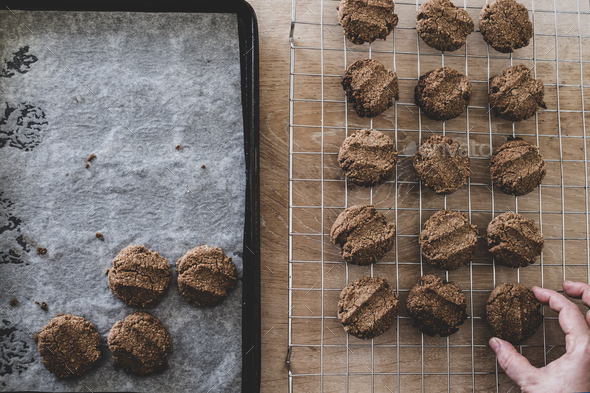 High angle close up of person removing freshly baked chocolate cookies from a baking tray. - Stock Photo - Images