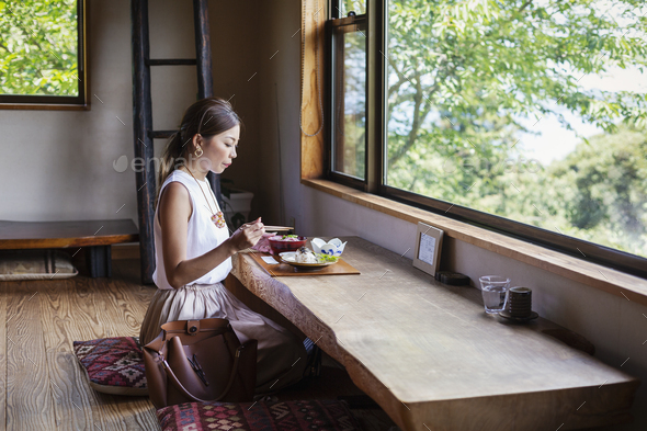 Japanese woman sitting at a table in a Japanese restaurant, eating. - Stock Photo - Images