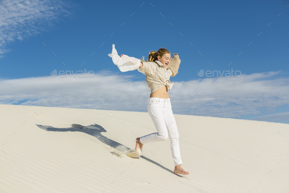 13 year old girl leaping and dancing in light white sand sand in a dunes landscape. - Stock Photo - Images