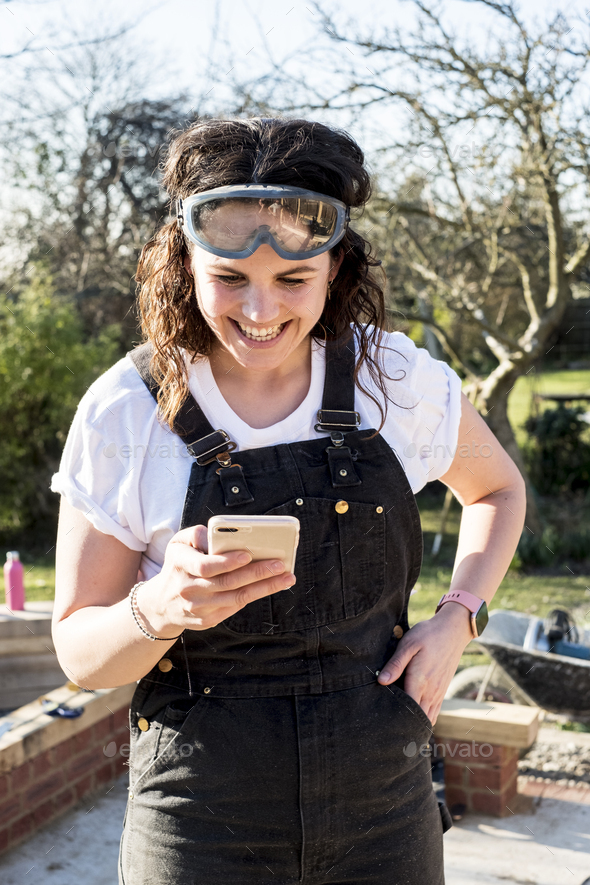 Smiling woman wearing dungarees and protective goggles checking her mobile phone. - Stock Photo - Images