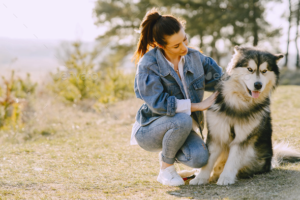 Stylish girl in a spring field with a dog - Stock Photo - Images