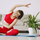 Girl in a red sports uniform make yoga at home - PhotoDune Item for Sale