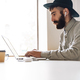 Photo of serious young man using laptop and earpods while sitting - PhotoDune Item for Sale