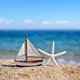 Miniature toy sailboat and starfish on the beach against the background of the sea and the blue sky - PhotoDune Item for Sale