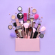 A pink cosmetics bag with professional makeup brushes and makeup products spilling out - PhotoDune Item for Sale