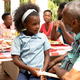 African American girl sitting on her grandfather knees during a family lunch in the garden - PhotoDune Item for Sale