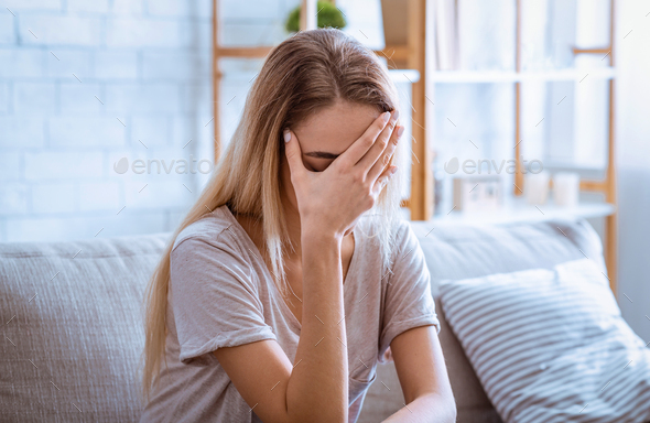 Sad woman covered face with hand. Stay alone at home - Stock Photo - Images