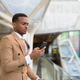 Young handsome African businessman using phone at footbridge in the city - PhotoDune Item for Sale