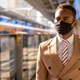 Young African businessman with mask thinking and waiting at the sky train station - PhotoDune Item for Sale
