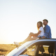 Young couple sitting on car and looking straight ahead. - PhotoDune Item for Sale