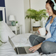 Cheerful pregnant woman listening music from the laptop - PhotoDune Item for Sale