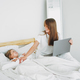 Mother freelancer with little daughter working on laptop in bed - PhotoDune Item for Sale