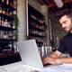 Male Owner Of Restaurant Bar Sitting At Counter Working On Laptop - PhotoDune Item for Sale