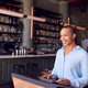 Female Owner Of Restaurant Bar Standing At Counter Using Digital Tablet - PhotoDune Item for Sale