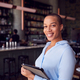 Portrait Of Confident Female Owner Of Restaurant Bar Standing By Counter Holding Digital Tablet - PhotoDune Item for Sale