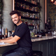 Portrait Of Male Owner Of Restaurant Bar Sitting At Counter Working On Laptop - PhotoDune Item for Sale