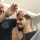 Hairstylist making men's haircut to an attractive man. - PhotoDune Item for Sale
