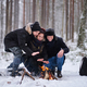 Friends of travelers bask in a fire in the snowy forest - PhotoDune Item for Sale