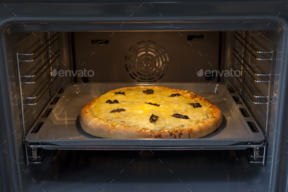Baking quattro formaggi pizza in oven with open door - Stock Photo - Images