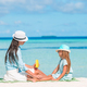 Young mother applying sun cream to daughter nose on the beach. Sun protection - PhotoDune Item for Sale