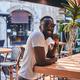 Smiling black man is sitting at cafe - PhotoDune Item for Sale