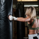 Portrait of female boxer on her training with punching bag - PhotoDune Item for Sale
