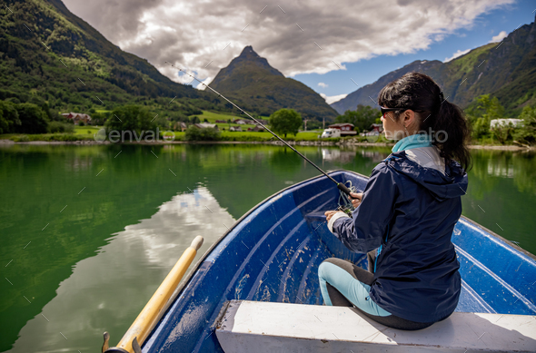 Woman fishing on a boat. - Stock Photo - Images