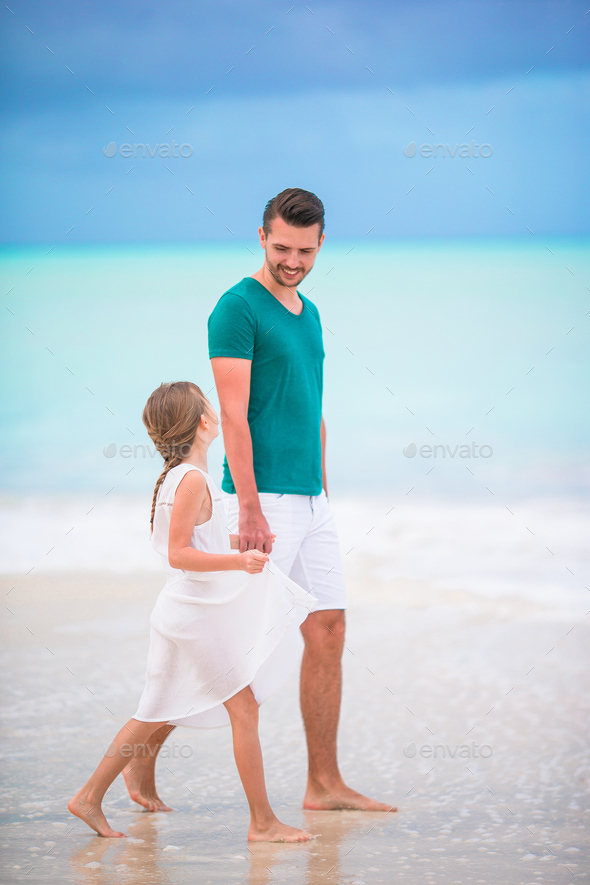 Happy father and his adorable little daughter at tropical beach walking together - Stock Photo - Images