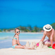 Family making sand castle at tropical white beach. Father and girl playing with sand on tropical - PhotoDune Item for Sale