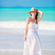 Young beautiful woman on white sand tropical beach. Caucasian girl with hat in dress background the - PhotoDune Item for Sale
