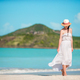 Young beautiful woman on tropical seashore. Happy girl relaxing at white sand tropical beach - PhotoDune Item for Sale