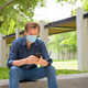 Young man with mask using phone and sitting at the park - PhotoDune Item for Sale