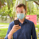 Face of young man using phone with mask and face shield for protection from corona virus outbreak at - PhotoDune Item for Sale