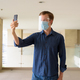 Young man with mask and face shield taking selfie at modern building - PhotoDune Item for Sale