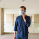 Young man with mask and face shield talking on the phone at modern building - PhotoDune Item for Sale