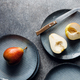 Blue food ceramic set with plates and pears over grey textured background - PhotoDune Item for Sale