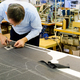 Tailor bending over a workbench cutting fabric - PhotoDune Item for Sale