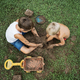 Top view of two brothers sitting on  grass playing with mud - PhotoDune Item for Sale