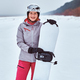 Smiling woman wearing warming sportswear posing with a snowboard on a snowy beach - PhotoDune Item for Sale