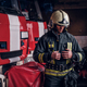 Fireman wearing protective uniform standing next to a fire engine in a garage of a fire department - PhotoDune Item for Sale