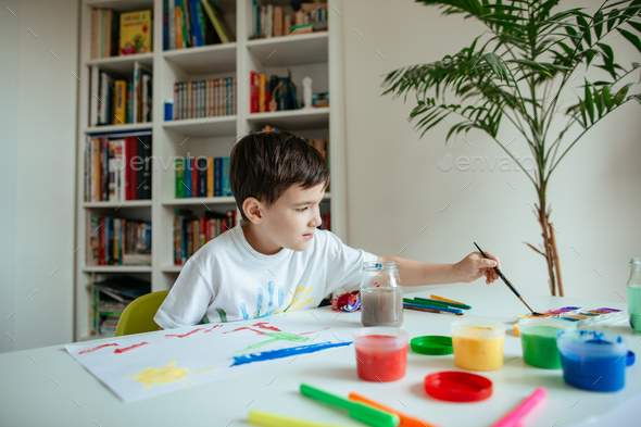 Schoolboy reaching for watercolor with paintbrush in his hand. - Stock Photo - Images